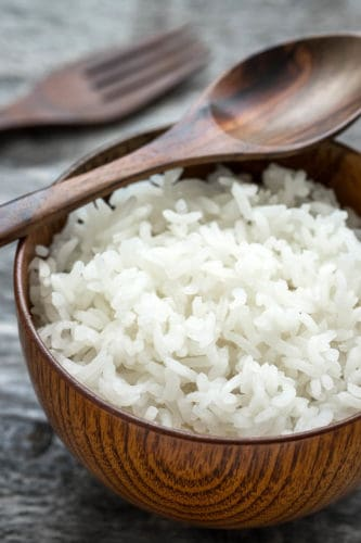 White sticky rice in a wooden bowl grey background