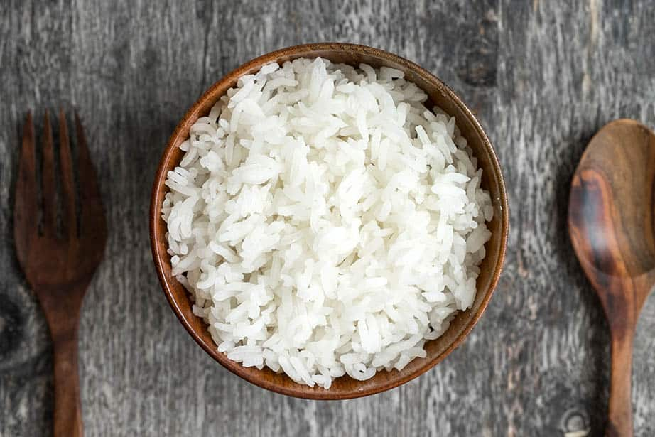 Overhead shot White sticky rice in a wooden bowl grey background