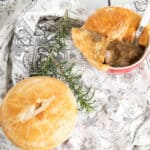 Square image two peppercorn meat pie on table clth