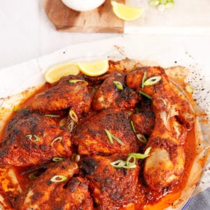 Peri Peri Chicken on a white background with lemon and aioli in the background