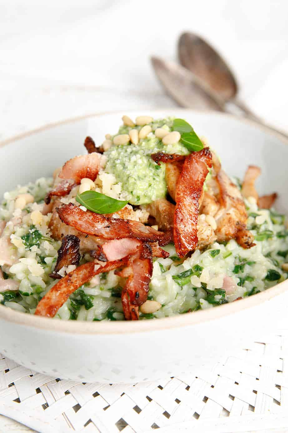A bowl of chicken risotto topped with pesto and bacon on white background