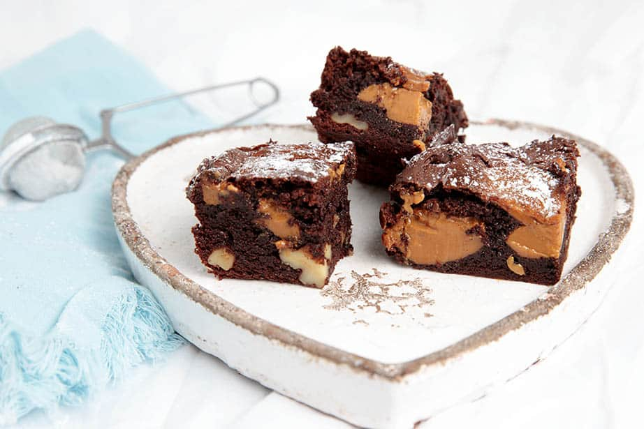 Landscape image of Caramel Chocolate Brownies on a plate and dusted with icing sugar
