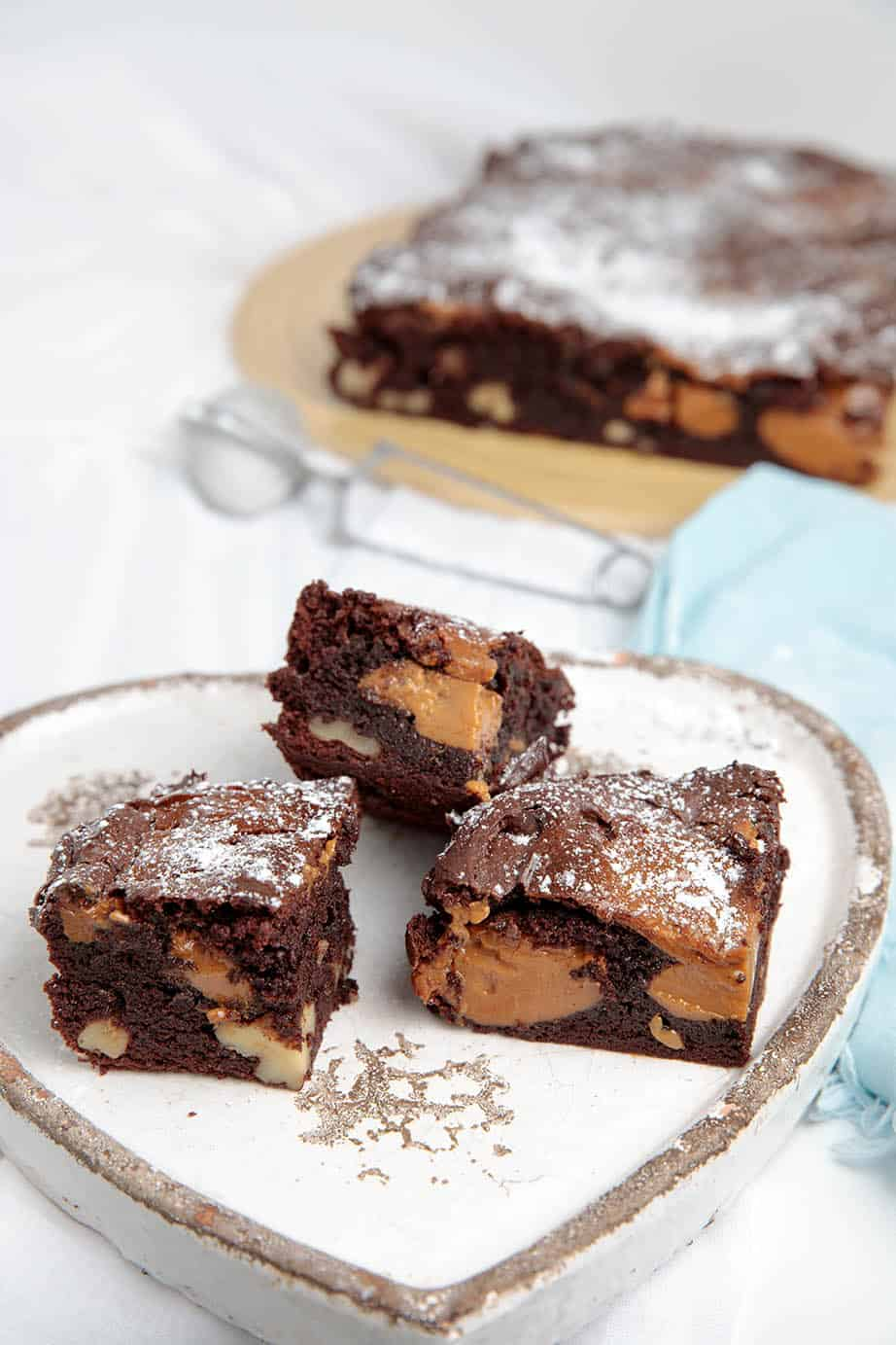 3 squares of Chocolate Caramel Brownie on a white platter with blue napkin