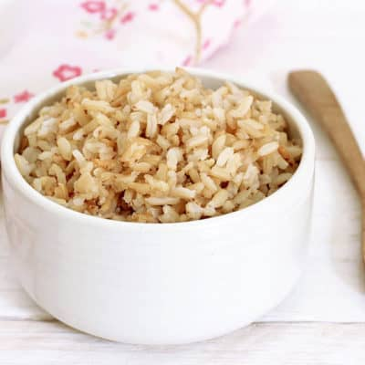 Cooked brown rice in a white bowl wooden spoon and floral serviette