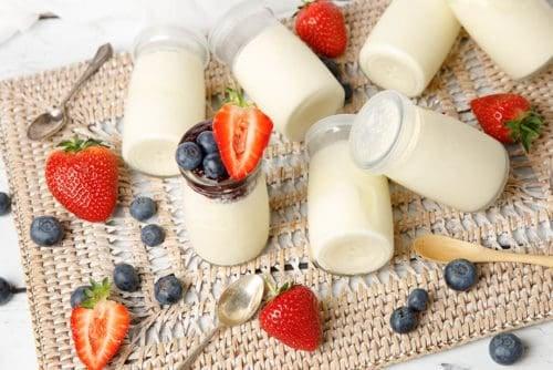 Landscape image yoghurt pots on a placemat with fruit