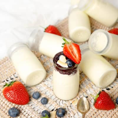 Glass yoghurt pots on a background with strawberries and blueberries