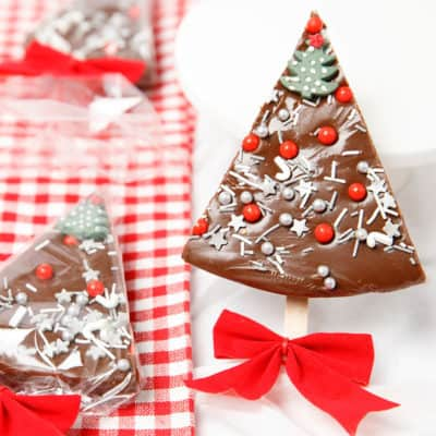 Peppermint chocolate fudge in the shape of a Christmas tree on white and red background
