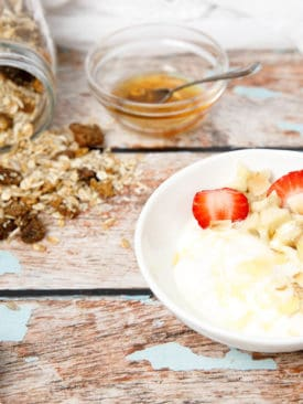 Yoghurt and muesli on a wooden table with fruit