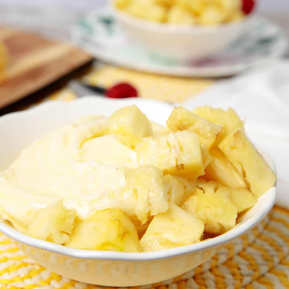 A bowl of pineapple dole whip with added cubed pineapple