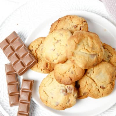 Overhead pic of choc chip cookies on a plate on pink blanket