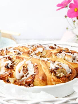 Cinnamon Scrolls in a white baking dish with pink flowers in the background