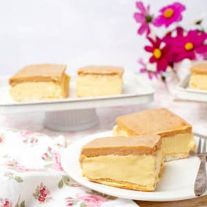 Landscape image of two Cadbury Caramilk Slices on a floral tablecloth