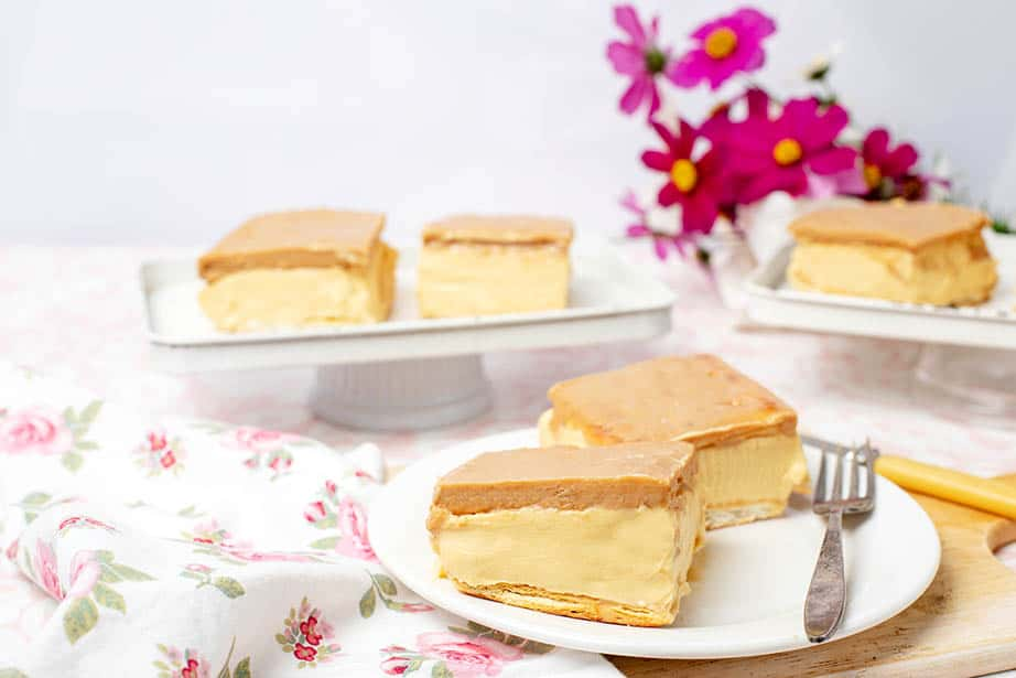 Landscape image of two Cadbury Caramilk Custard Slice on a floral tablecloth