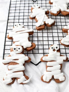 Gingerbread men decorated with icing to ;ook like mummy cookies for Halloween