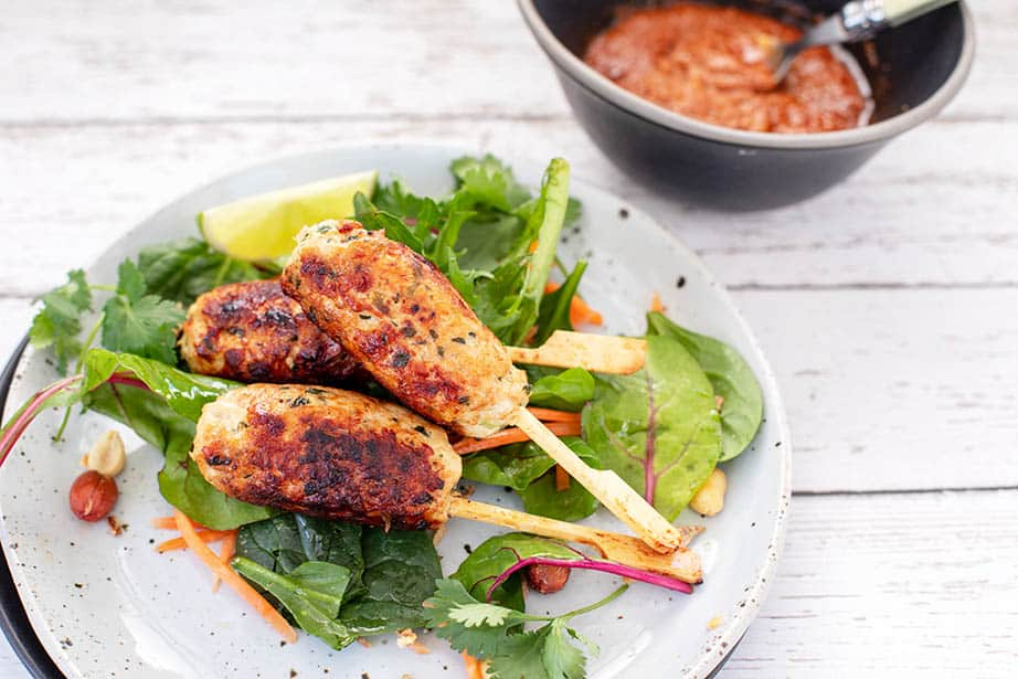 Close up image of Keto chicken kebab served with salad greens and peanut sauce in a bowl on the side