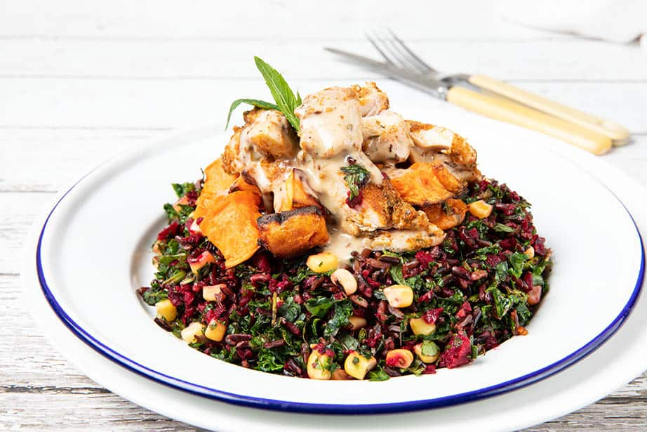 Chicken salad bowl - chicken on a bed of kale and raw salad ingredients