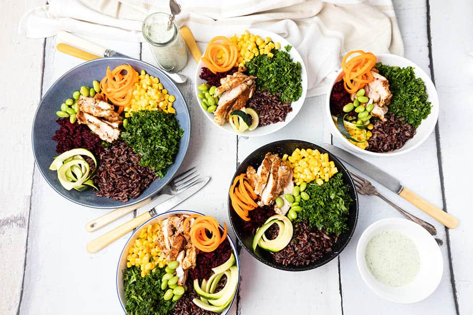 Overhead image of 5 Chicken salad bowls on a wooden background