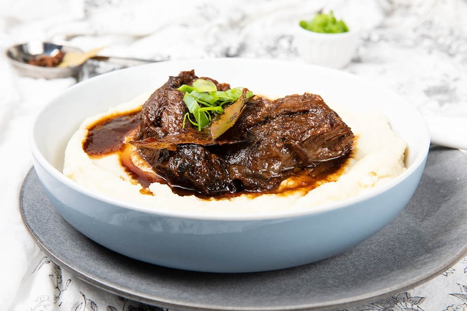 Large bowl of mashed potato covered in slow cooked beef cheeks