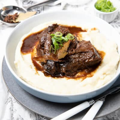 Large bowl of mashed potato covered in slow cooked beef cheeks on a cloth background