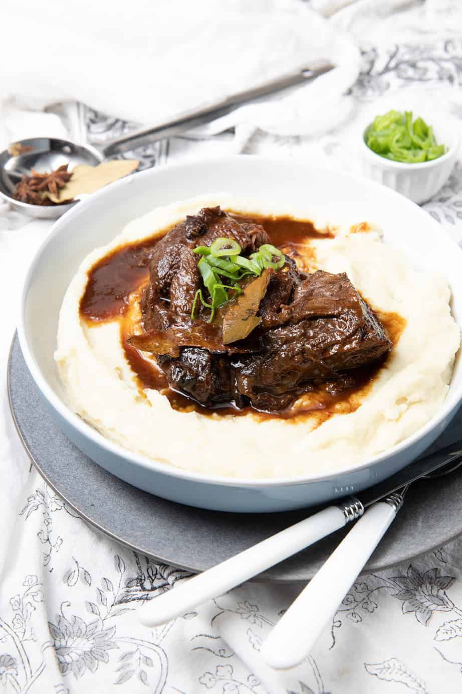 Large bowl of mashed potato with a serving of slow cooked beef cheeks over the top