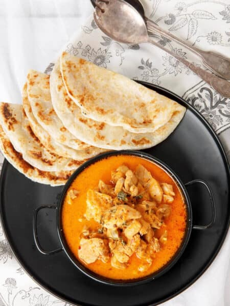 Kashmiri Chicken Curry on a black plate with roti