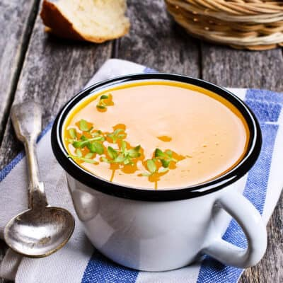 Pumpkin soup in a cup on a wooden background