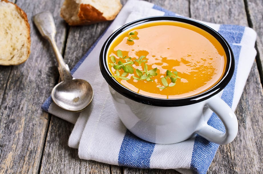 Cup of pumpkin soup on a wooden table with spoon and bread