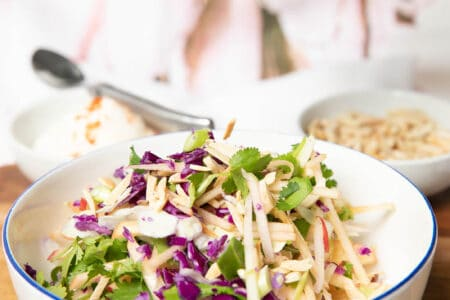 Apple coleslaw in a bowl and a hand adding slivered almonds