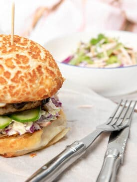 A Thermomix Burger on a white table setting with coleslaw