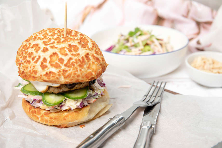 A pork burger on a roll with coleslaw in the background, knife and fork.