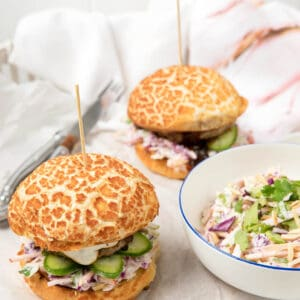 Two pork burgers on a white background with a bowl of slaw.