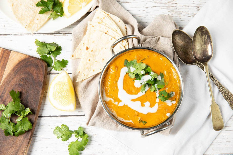 Overhead landscape image of vegan red lentil dahl served with coriander and coconut cream.